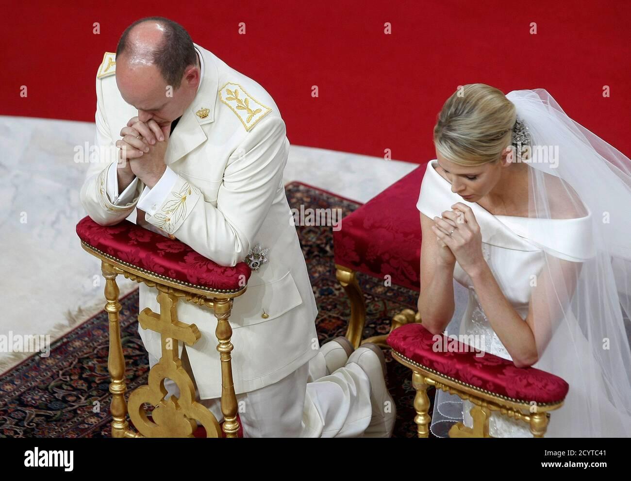Monacos Fürst Albert II. (L) und Prinzessin Charlene knien am Altar während ihrer religiösen Hochzeitszeremonie im Palast von Monaco am 2. Juli 2011. REUTERS/Lionel Cironneau/Pool (MONACO - Tags: ROYALS UNTERHALTUNG BILD DES TAGES TOP PICTURE) Stockfoto