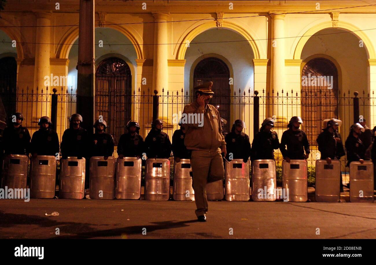 Paraguayischen Polizist spricht über sein Mobiltelefon vor einer Reihe von Riot Policement außerhalb des Kongresses in Asuncion, 22. Juni 2012. Aus dem Amt entfernt Kongress Paraguays Präsident Fernando Lugo am Freitag nach einem blitzschnellen Anklage, die er sagte gleichbedeutend mit einem Staatsstreich war aber zugesagt, zu akzeptieren. Lugo, ein Silber-behaarten ehemaliger römisch-katholischer Bischof, die die Kirche für das Präsidentenamt, beendet war schuldig Misshandlung bewaffnete Auseinandersetzungen über ein Land Räumung in denen 17 Polizei und bäuerliche Landwirte letzte Woche getötet wurden.  REUTERS/Marcos Brindicci (PARAGUAY - Tags: Politik Kriminalität Gesetz) Stockfoto