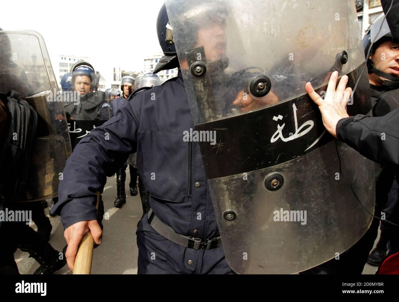 Ein Anti-Regierungs-Demonstranten drängt zurück Riot Policement während einer Demonstration in Algier 19. Februar 2011. Algerische Polizei in Kampfmontur am Samstag umgeben etwa 500 Demonstranten versucht, einen Marsch durch die Hauptstadt inspiriert durch Aufstände in anderen Teilen der arabischen Welt unter Missachtung eines Verbots zu inszenieren.  REUTERS/Zohra Bensemra (Algerien - Tags: Politik Unruhen) Stockfoto