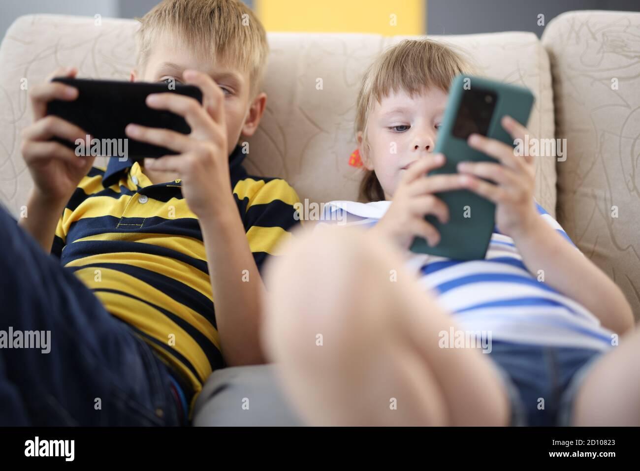Kinder halten das mobile Gerät in den Händen und spielen. Stockfoto