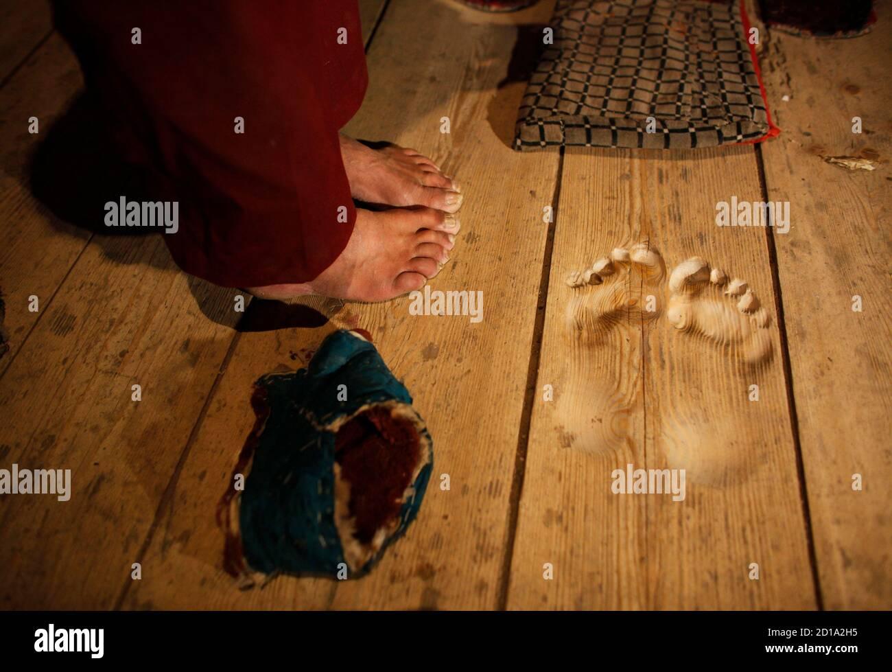 Die Füße des Mönchs Hua Chi sind in der Nähe die Fußabdrücke von ihm gemacht, indem Sie beten an der gleichen Stelle seit Jahrzehnten in einem Kloster in der Nähe von Tongren, Qinghai Provinz 25. Februar 2009 gesehen. Hua Chi, wer, dass er etwa 70 Jahre alt ist glaubt, hat an der gleichen Stelle betete so viele Male, dass perfekte Fußabdrücke auf der hölzernen Tür bleiben. Der Mönch und Arzt der traditionellen Medizin wurde in den kleinen Tempel in der Kloster-Stadt Tongren in Chinas westliche Qinghai Provinz seit fast zwanzig Jahren zu eine strengen persönlichen Ritual durchzuführen, kommen. Jeden Tag kommt vor Sonnenaufgang, Hua Tempel di Spagna, Platzierung Stockfoto