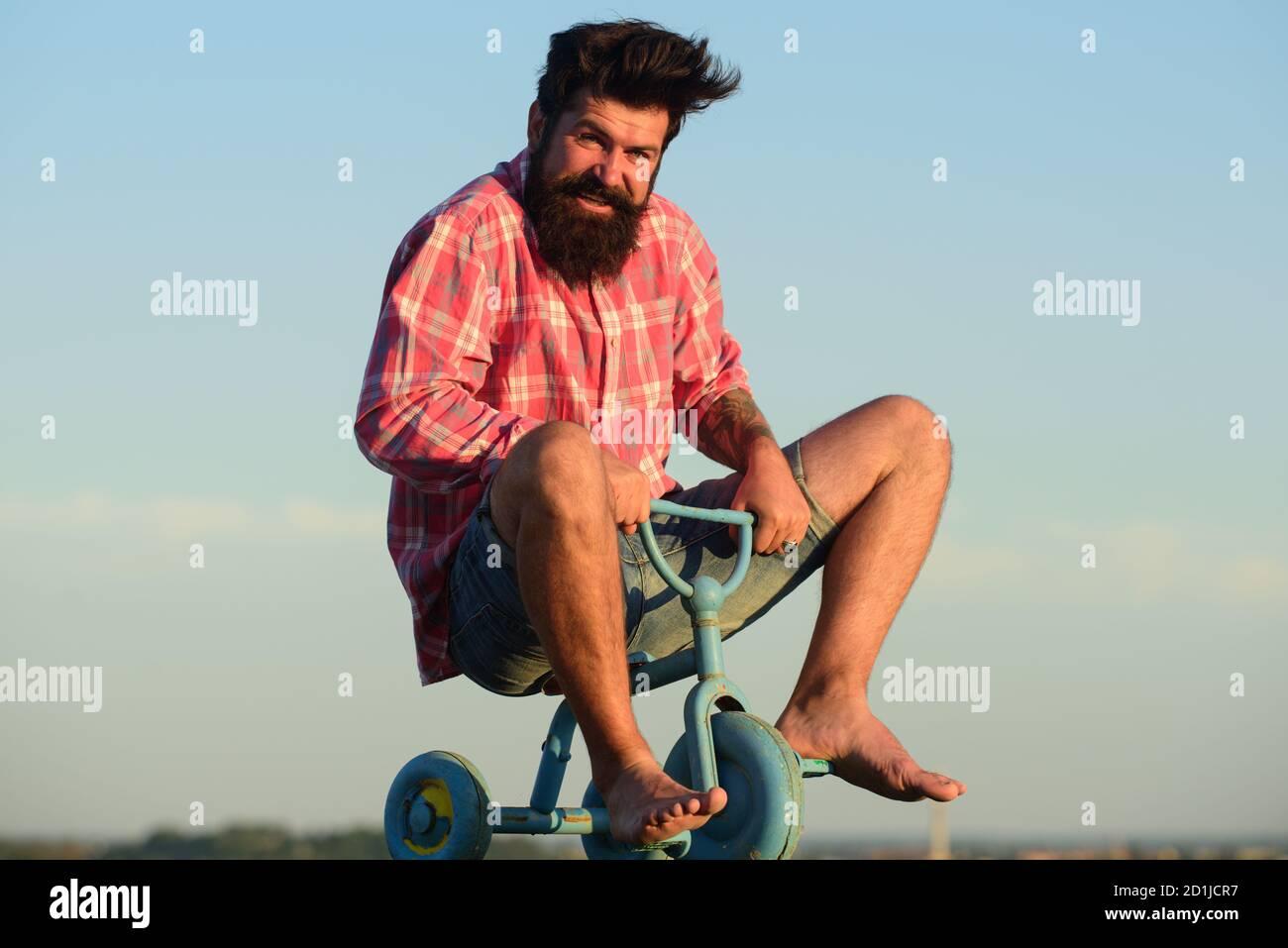 Mann, der sich wie ein Kind verhält. Lustiger Mann auf einem Kinderfahrrad. Nerdy Radfahrer Reiten. Stockfoto