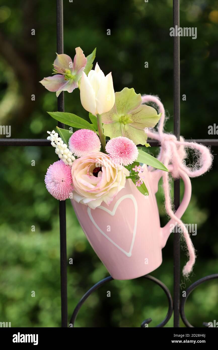 Romantisches Bouquet von weißen und rosa Frühlingsblumen in Tasse Stockfoto
