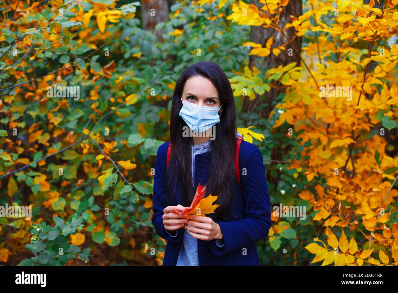 Schöne Frau in Schutzmaske hält Ahornblätter in bunten Herbstwald. Neues normales Konzept. Stockfoto
