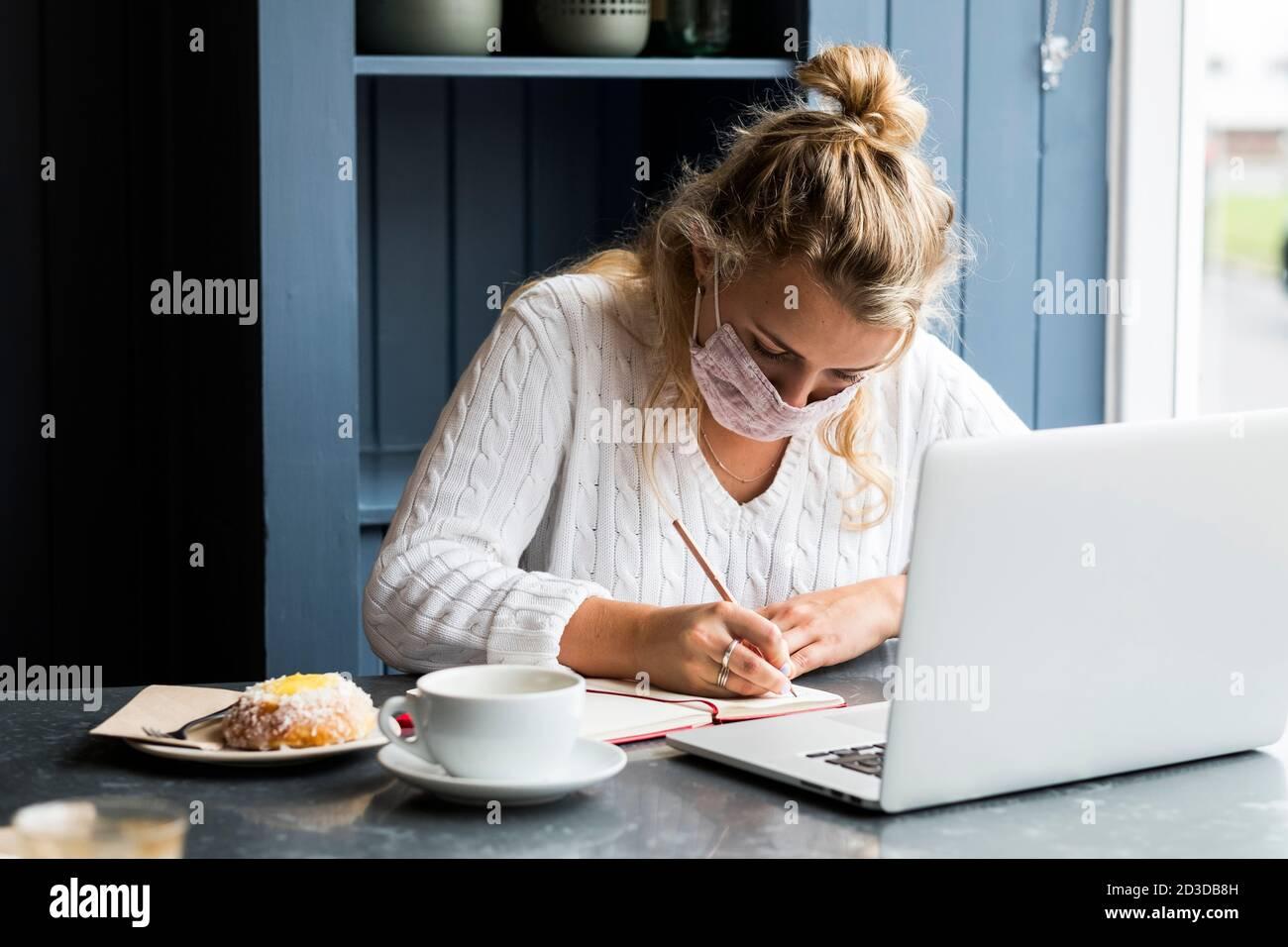 Junge blonde Frau trägt Gesichtsmaske allein sitzen an einem Café-Tisch mit einem Laptop-Computer, schriftlich in Notizbuch, arbeiten aus der Ferne. Stockfoto