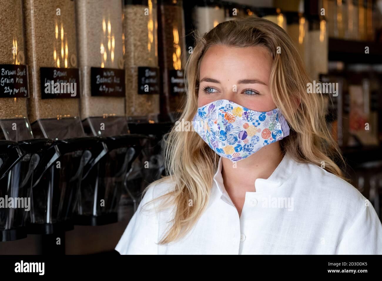 Portrait der jungen blonden Frau trägt Gesichtsmaske, stehen in Abfall freien Vollwertspeicher. Stockfoto