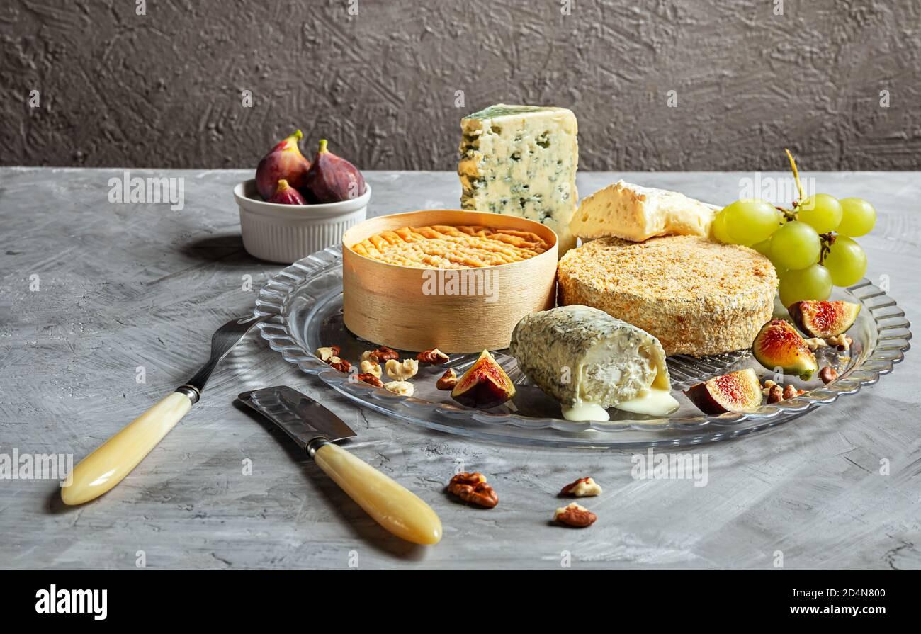 Auswahl an französischem Käse - Camembert, roquefort, Brie, Ziegenkäse und Epoisse mit Trauben, Feigen und Nüssen auf grauem Hintergrund Stockfoto