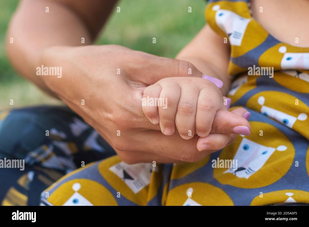 Eine Babyhand hält die Hand der Mutter. Glückliches Familien- und Babyschutzkonzept Stockfoto