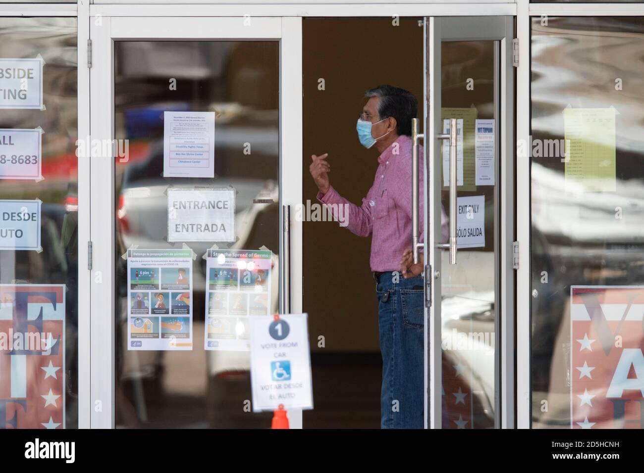 Austin, TX USA, 13. Oktober 2020: Der Wahlhelfer Rogelio Cipriano hält die Tür, als die Wähler am ersten Tag der vorzeitigen Abstimmung in Texas ein- und aussteigen. Regierungsvertreter der Landtagswahlen berichten von Rekordzahlen früher Wähler und nur geringfügigen Verarbeitungsproblemen, da bis Mittag 14,000 Stimmzettel abgeworfen wurden. Kredit: Bob Daemmrich/Alamy Live Nachrichten Stockfoto