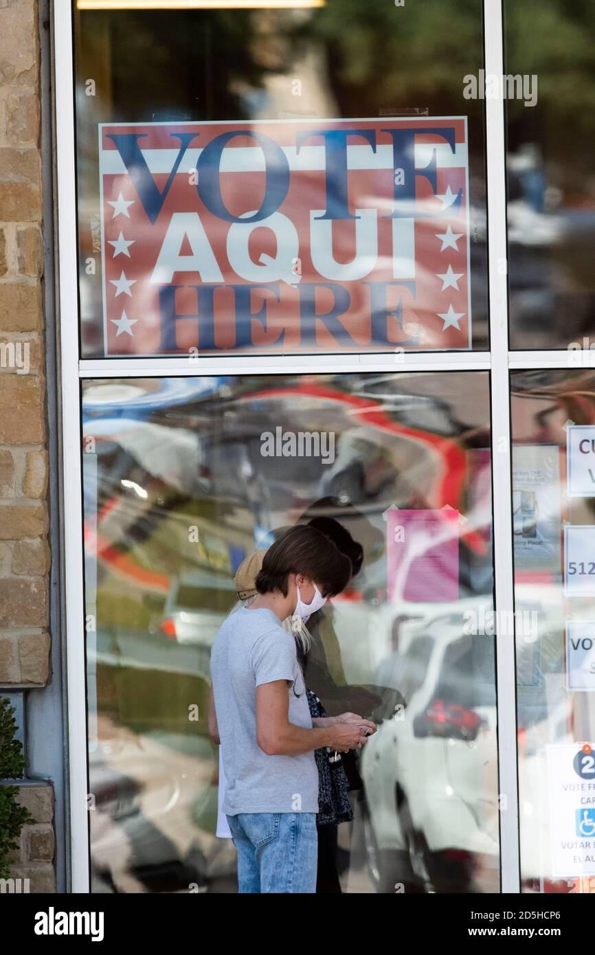 Austin, TX USA, 13. Oktober 2020: Verzerrte Spiegelungen von Autos und Menschen springen am ersten Tag der frühen Abstimmung aus den Fenstern eines Wahllokale in Nord-Austin. Regierungsvertreter der Landtagswahlen berichten von Rekordzahlen früher Wähler und nur geringfügigen Verarbeitungsproblemen, da bis Mittag 14,000 Stimmzettel abgeworfen wurden. Kredit: Bob Daemmrich/Alamy Live Nachrichten Stockfoto