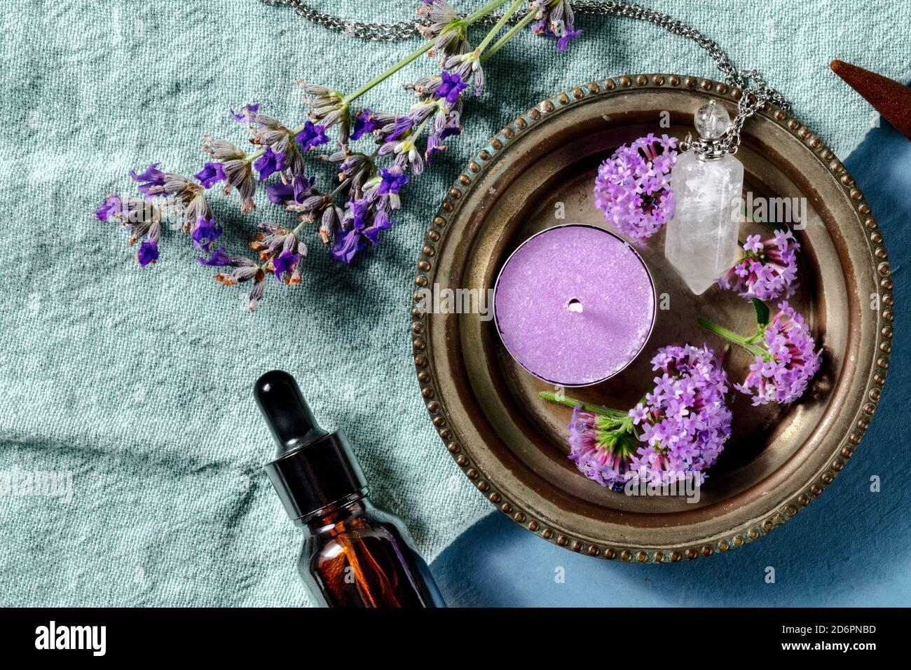 Ätherisches Öl und sein Nutzungskonzept mit Kopierraum. Aromatische Kerze und ein Fläschchen für Parfüm Lavendel und Vervain, von oben auf blauem Hintergrund geschossen Stockfoto
