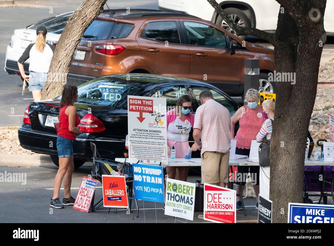 Austin, TX USA, Okt. 13 2020: Befürworter für Kandidaten und Stimmzettel bieten Wählern Informationen außerhalb der gesetzlich zulässigen 100-Fuß-Linie von einem Wahllokal Eingang an einem Ort der vorzeitigen Abstimmung für die Präsidentschaftswahl 2020. Stockfoto