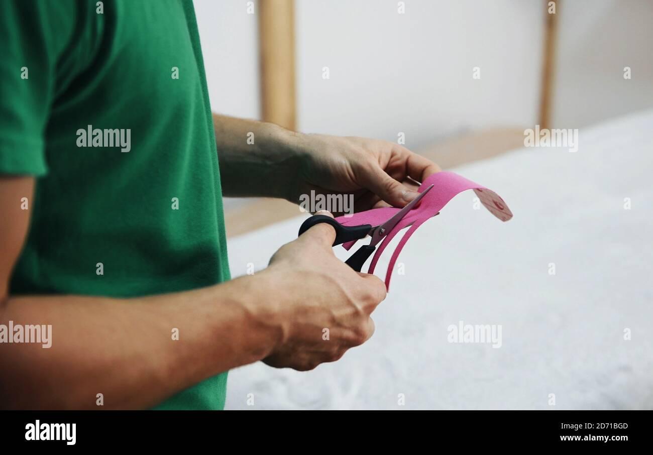 Nahaufnahme der Hände des Arztes mit einer Schneideschere Pinkes Kinesio-Band Stockfoto