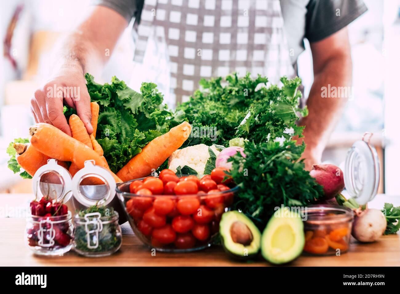 Nicht erkennbarer Erwachsener mit viel Gemüse auf dem Tisch - gemischte bunte Saison Lebensmittel und Früchte für Vegetarier oder Vegane Menschen - gesundes Livestyl Stockfoto