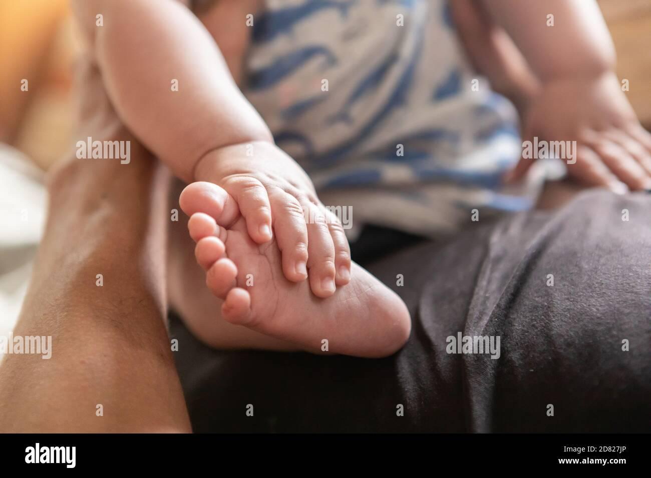 Selektive Fokussierung der Hände, die Beine und Füße des Babys berühren Junge während der Ruhe und sitzen auf seinem Vater Bauch mit Unterstützung zu Hause Stockfoto