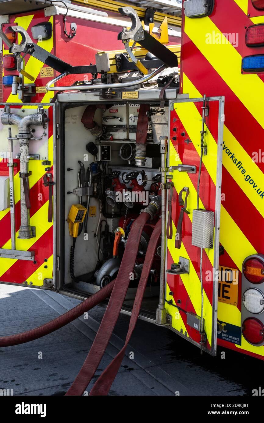 Die Rückansicht eines englischen Feuerwehrmotors mit den Pumpen, den Schläuchen und den verschiedenen Brandbekämpfungseinrichtungen an Bord Stockfoto