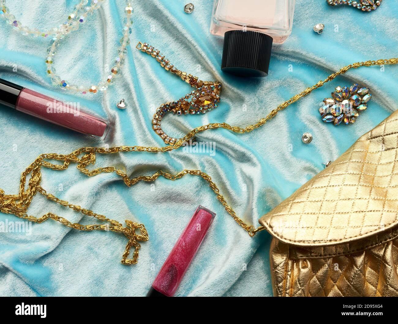goldene Handtasche, Lipgloss und Perlen auf blauem Hintergrund, Draufsicht. Stockfoto