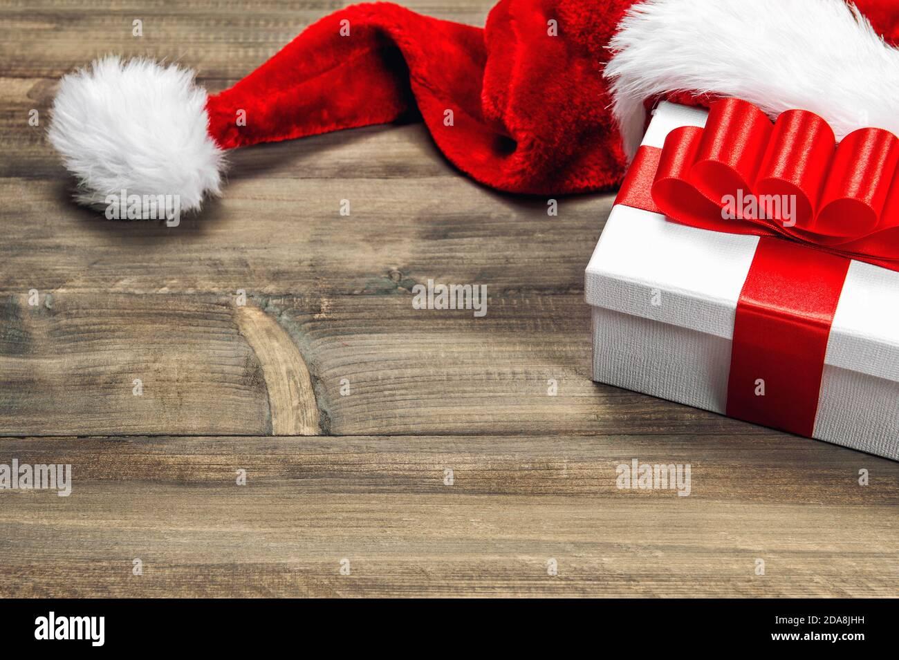 Weihnachtsdekorationund Geschenkbox mit roter Schleife auf Holz Hintergrund Stockfoto