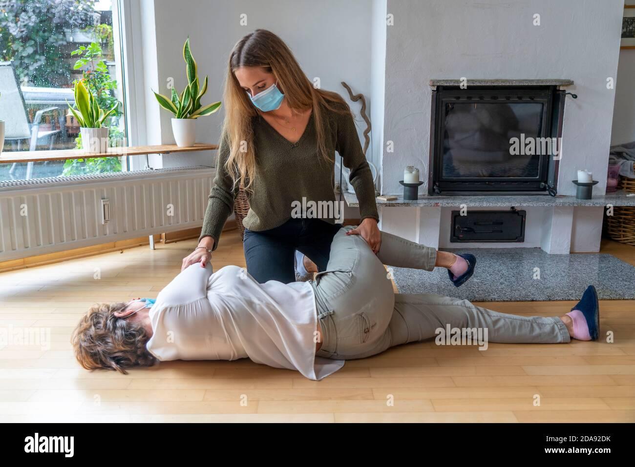 Erste Hilfe Massnahmen unter Corona-Bedingungen, stabile Seitenlage, nach einem Fall im der Wohnung, mit Mund-Nase-Maske, beim Ersthelfer Leistung Stockfoto