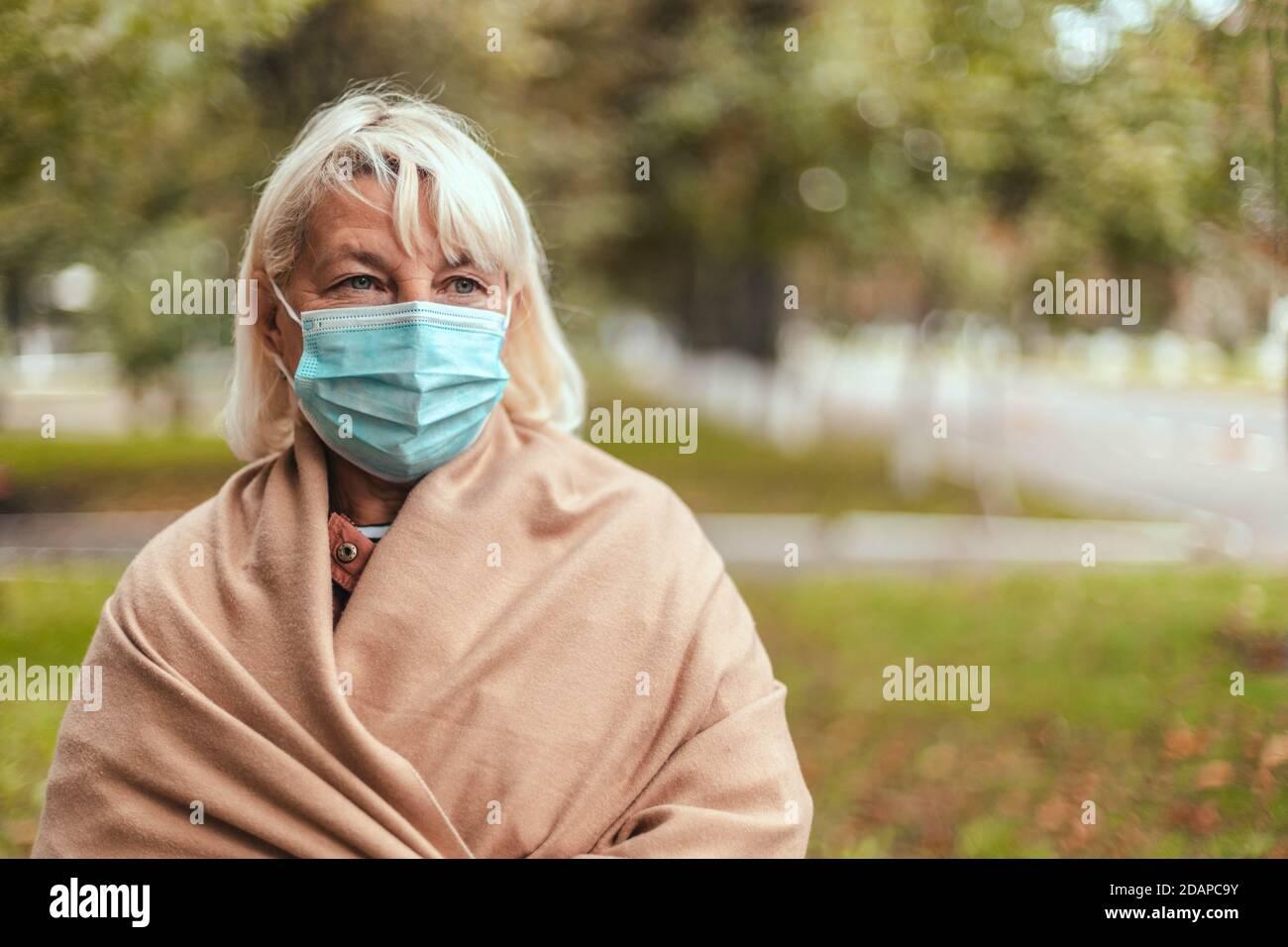 Frau trägt schützende Gesichtsmaske und in einem warmen Kaschmir Schal im Park im Freien während Quarantäne von Coronavirus Pandemie. Kopieren, leerer Platz für Text Stockfoto