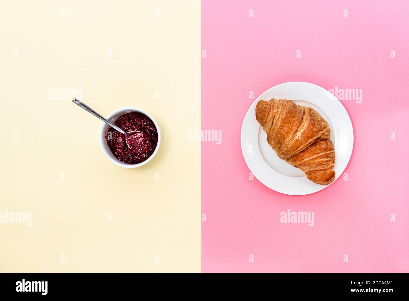 Croissant und eine Kanne Marmelade auf einem gespaltenen rosa und cremefarbenen Hintergrund. Stockfoto