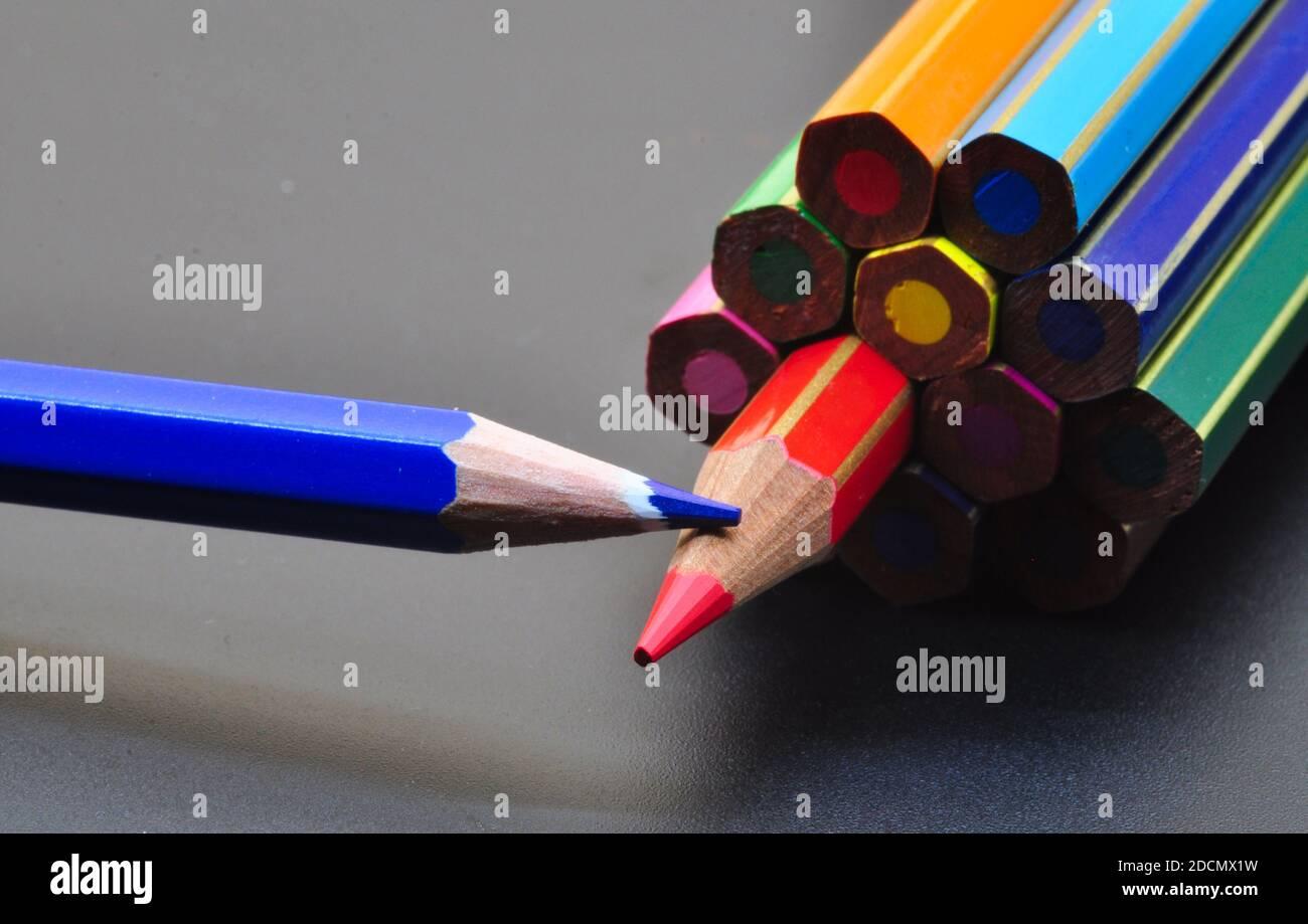 Metapher für Strategie und Teamwork, dargestellt durch Farbstifte auf schwarzem Hintergrund, die das Konzept des Denkens außerhalb des Tisches darstellen. Stockfoto