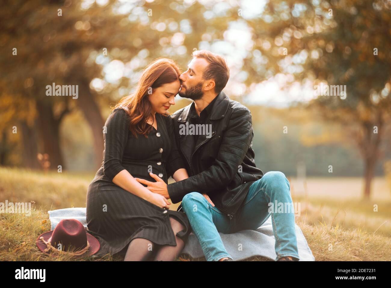 Foto von glücklichen schwangeren Paar auf der Bank im Park sitzen, schöne Stirn Kuss. Stockfoto
