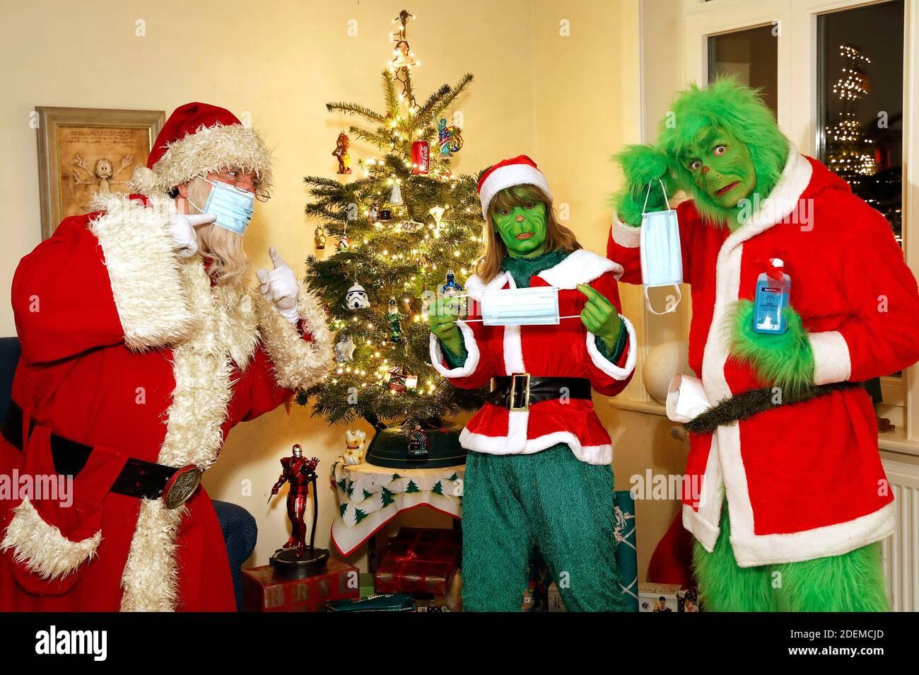 Der Weihnachtsmann versucht dem Grinch und Frau Grinch zu erklären, wie man eine Schutzmaske trägt. GEEK ART - Bodypainting und Transformaking: 'Der Grinch stiehlt Weihnachten' Fotoshooting mit Enrico Lein als Grinch, Maria Skupin als Frau Grinch und Fabian Zesiger als Weihnachtsmann in der Villa Czarnecki. In Hameln am 30. November 2020 - EIN Projekt des Fotografen Tschiponnique Skupin und des Bodypainters Enrico Lein Stockfoto