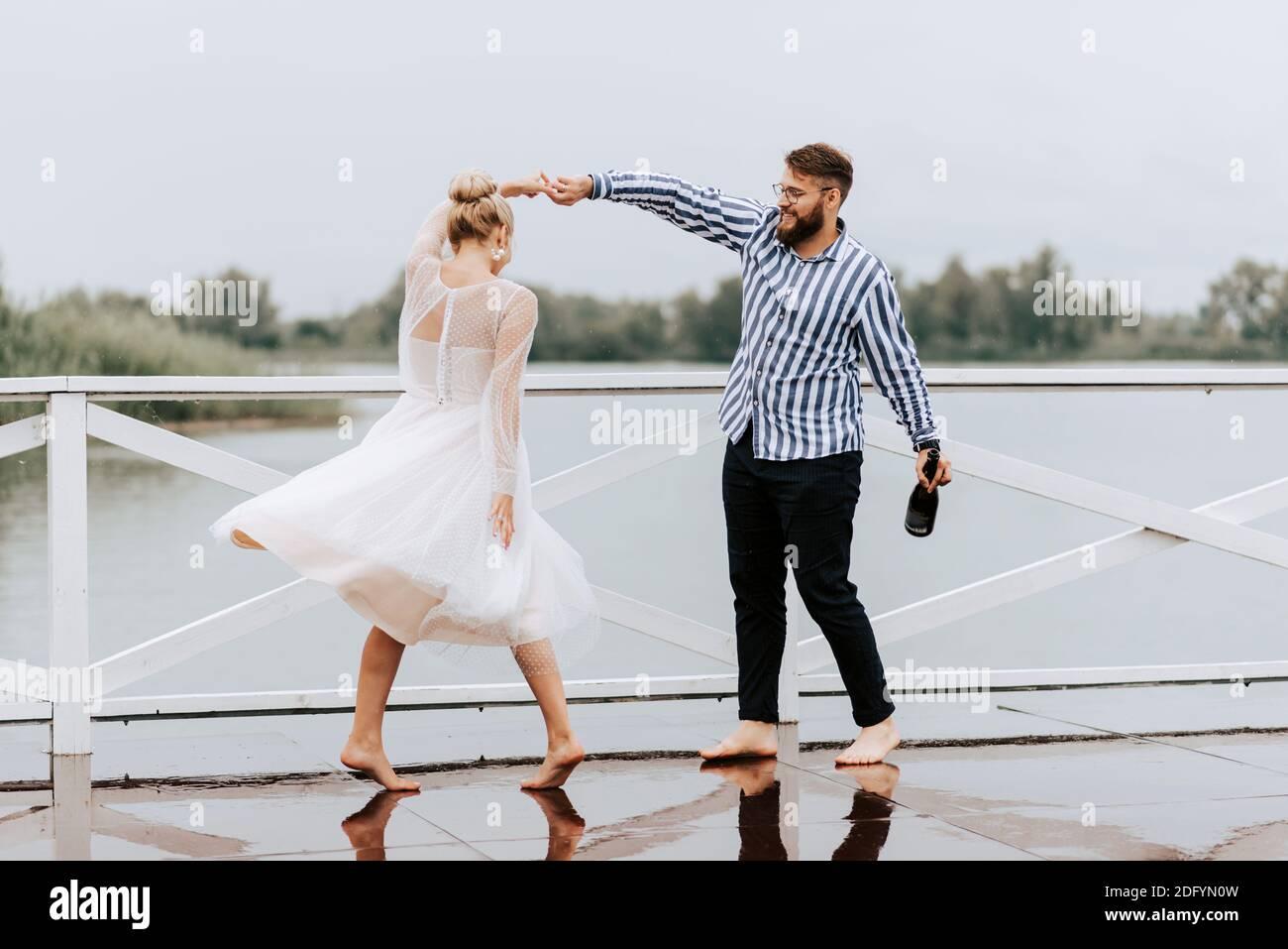 Ein Mann und eine Frau tanzen barfuß und haben Spaß auf dem Kai am See. Stockfoto