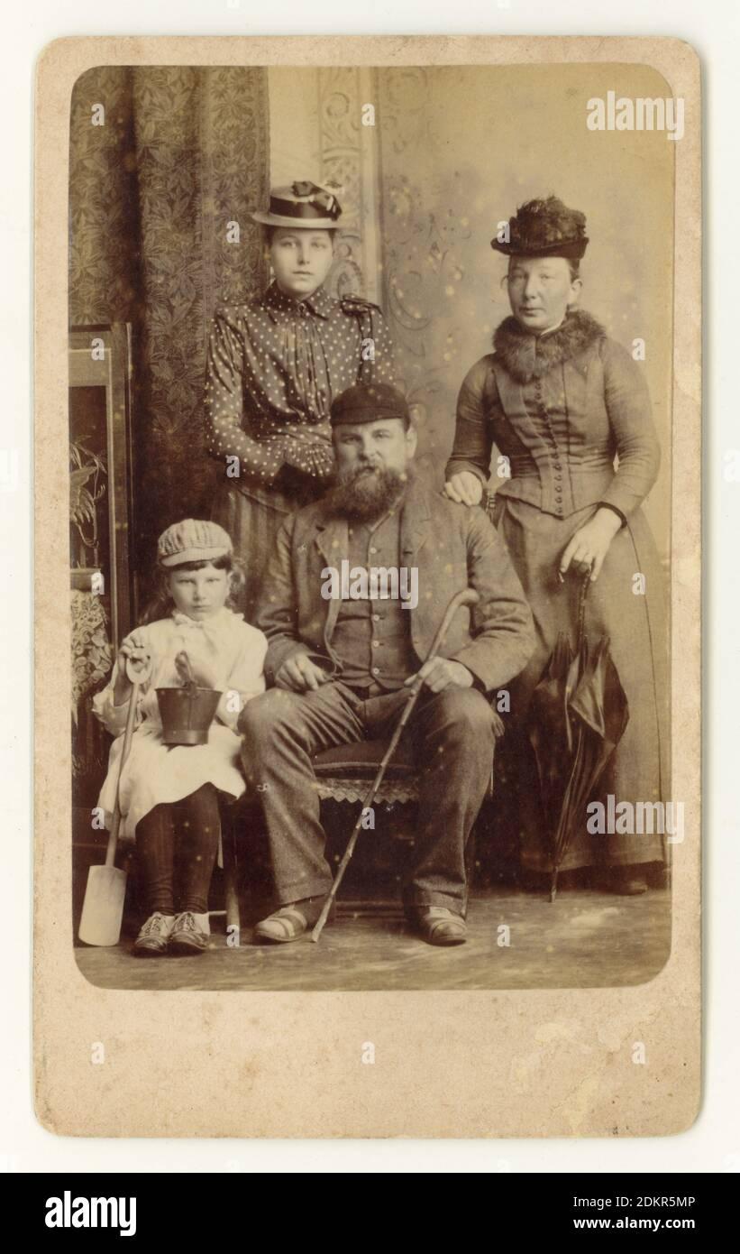 Original charaktervolles viktorianisches CDV (Carte de Visite) Erinnerungsfoto einer Arbeiterfamilie mit Schwiegermutter im Urlaub im Badeort Skegness, Lincolnshire, England, U.K. um 1888. Das Kind, das einen Eimer und Spaten hält, trägt eine merkwürdige Mischung aus Mädchenkleid und Knabenmütze und ist angesichts der viktorianischen Gewohnheit, Jungen in Mädchenkleidung zu kleiden, wahrscheinlich ein Junge. Er sieht nicht sehr glücklich aus und lässt sein Foto offenbar unter Zwang machen. Stockfoto