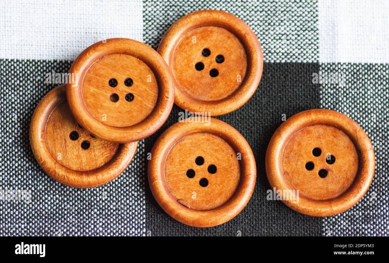 Runde braune Nähknöpfe aus Holz isoliert auf textilen Hintergrund. Draufsicht . Nahaufnahme. Makro. Stockfoto