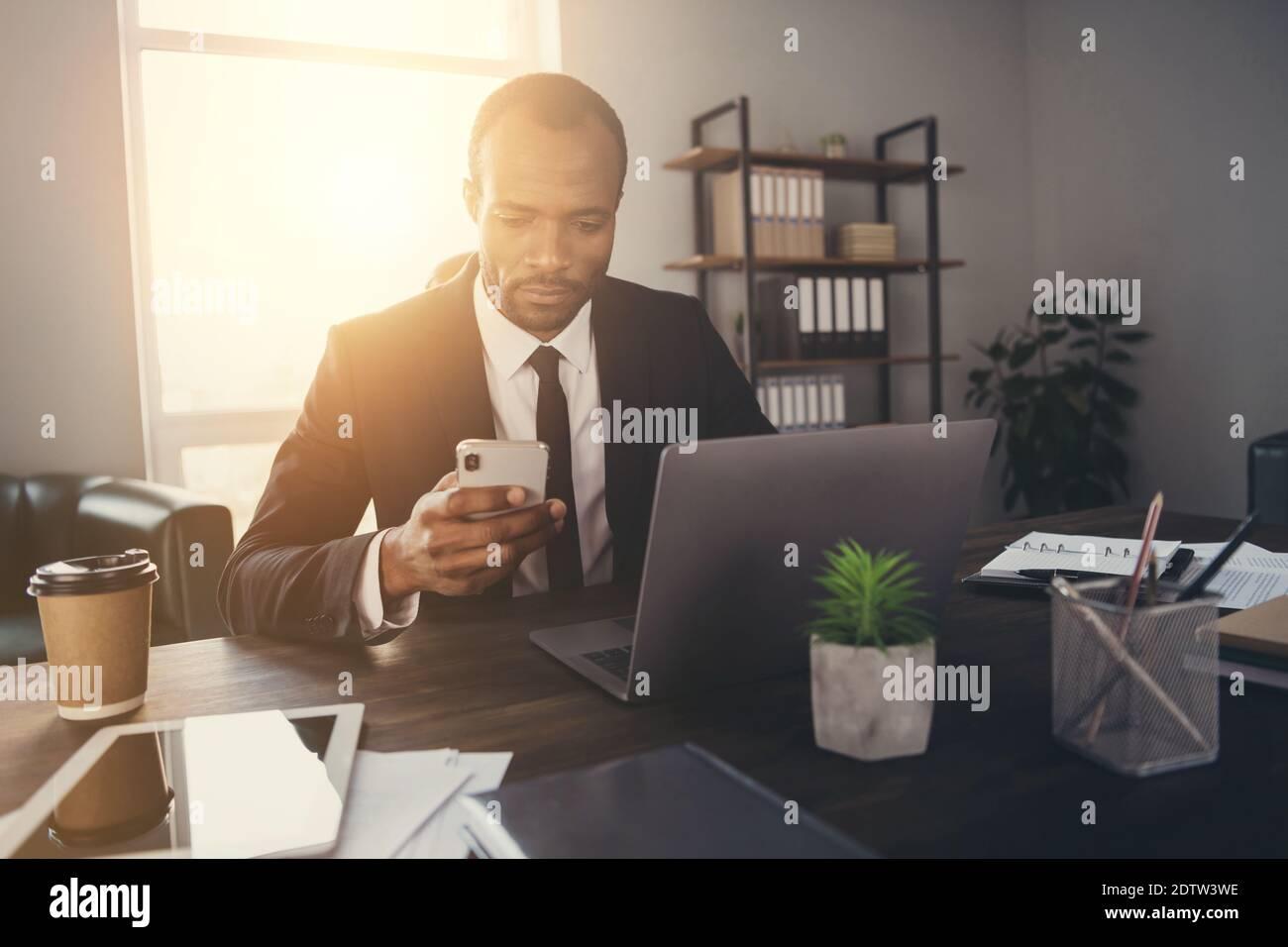 Portrait von fokussierten nachdenklichen afro amerikanischen Mann Broker Rechtsanwalt verwenden Smartphone Chat mit Kunden Partner tragen Anzug Tuxedo in Arbeitsplatz Stockfoto