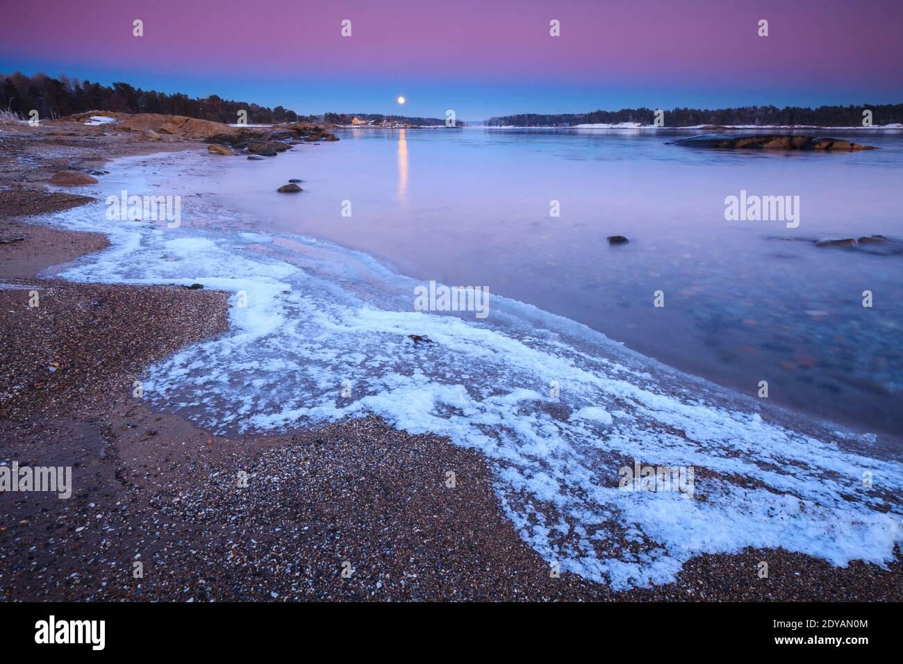 Schöner Winterabend mit Mondaufgang und Erdschatten, im Ofen in Råde, am Oslofjord, Østfold, Norwegen. Stockfoto
