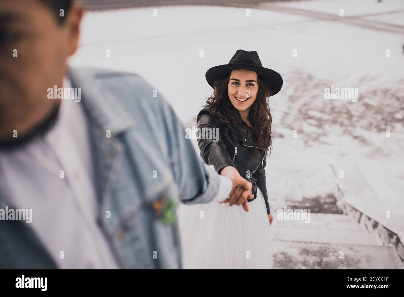 Mexikanischer hispanischer Mann in übergroßer Jeansjacke und Frau in hut Leder Biker Jacke küssen Umarmung lachend walking.groom Braut Hochzeit Ich liebe das Paar Stockfoto