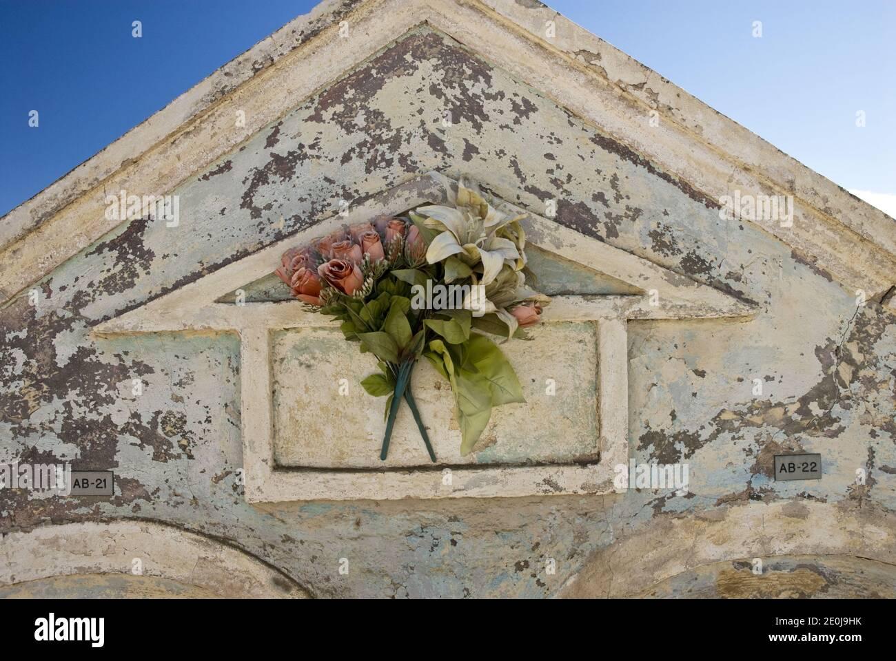 Blumen schmücken Krypten auf dem Friedhof neben der historischen und bunten St. Anna's Catholic Church, Noord, Aruba. Stockfoto