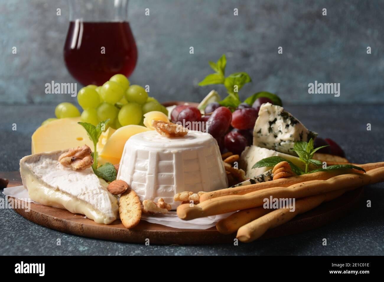 Käseplatte mit verschiedenen Käsesorten, Trauben, Nüssen und Snacks. Italienische, französische Käsespeise. Traditionelles Shavuot jüdisches Feiertagsessen Konzept Stockfoto