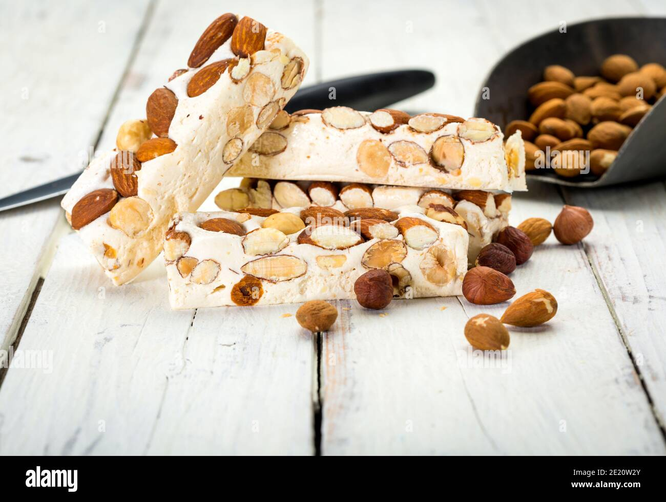 Turron-Blöcke mit Mandeln und Haselnüssen auf rustikalem Holztisch Mit Messer und Schaufel Stockfoto