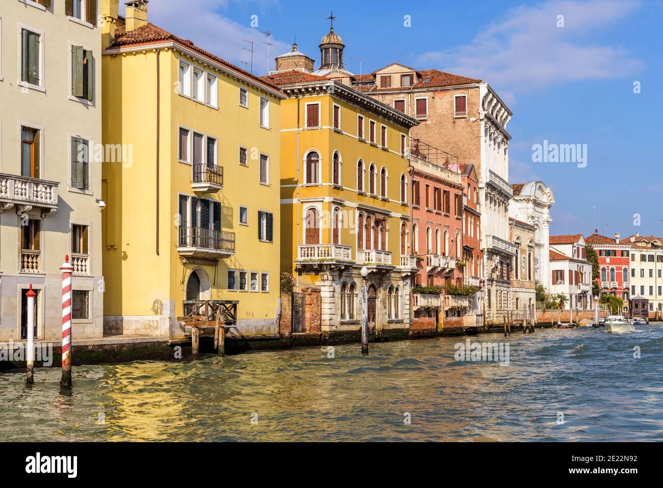 Colourful Canal - Helles Sonnenlicht am Nachmittag scheint auf bunten historischen Gebäuden am Ufer des Canale Grande. Venedig, Italien. Stockfoto