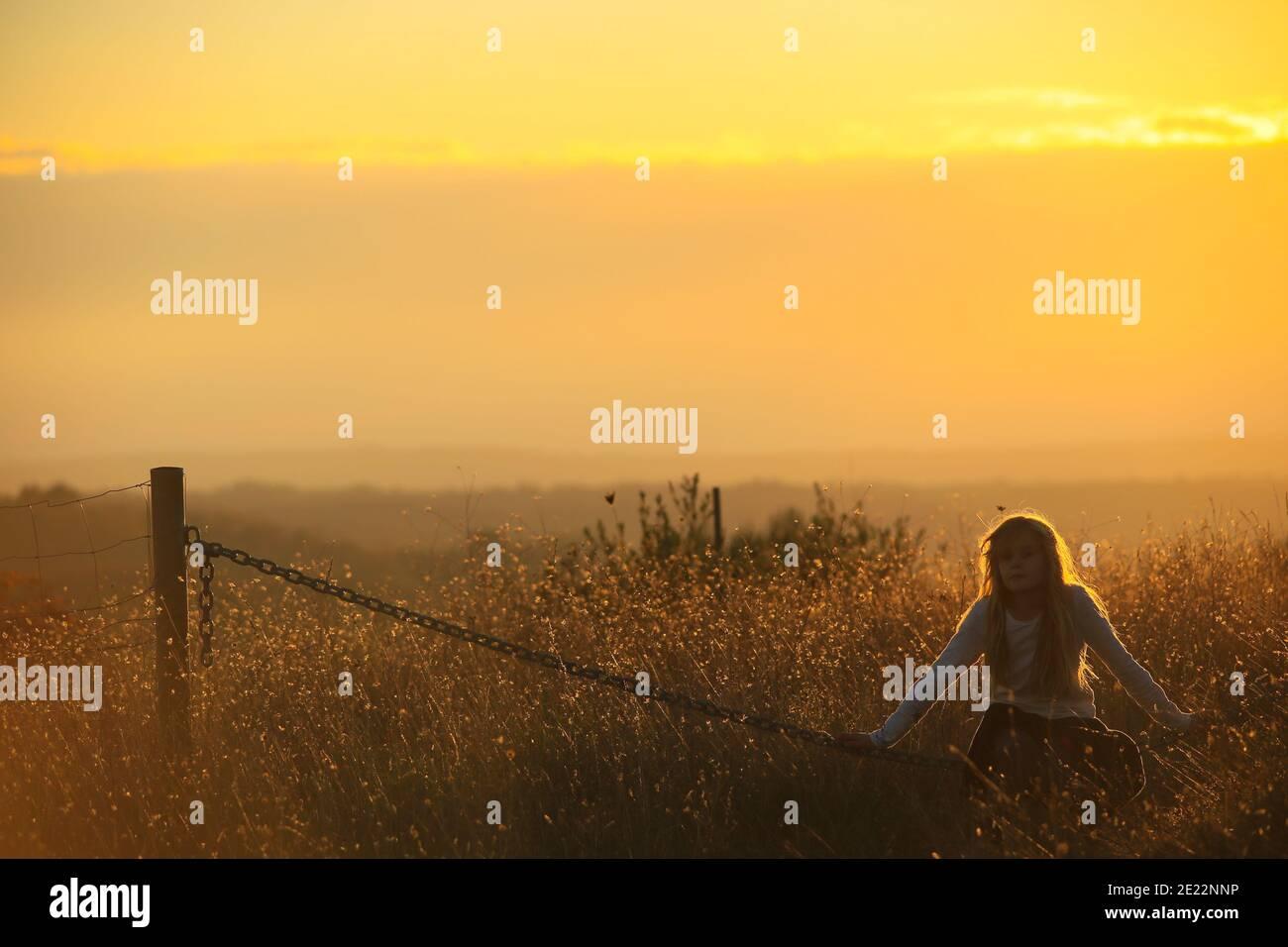 Junge Blonde Mädchen sitzt auf einer Kette in einem goldenen Sonnenuntergang Stockfoto