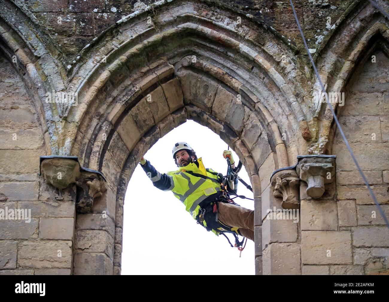 Der Steinmetz James Preston von SSH Conservation, abseils von Rievaulx Abbey in North Yorkshire als English Heritage bereitet sich auf die Durchführung von lebenswichtigen Naturschutzarbeiten vor. English Heritage beauftragt eine Untersuchung der Abtei Rievaulx in einem fünfjährigen Zyklus, um den Zustand der Abtei vom Boden bis zur Spitze der Struktur zu beurteilen. Stockfoto