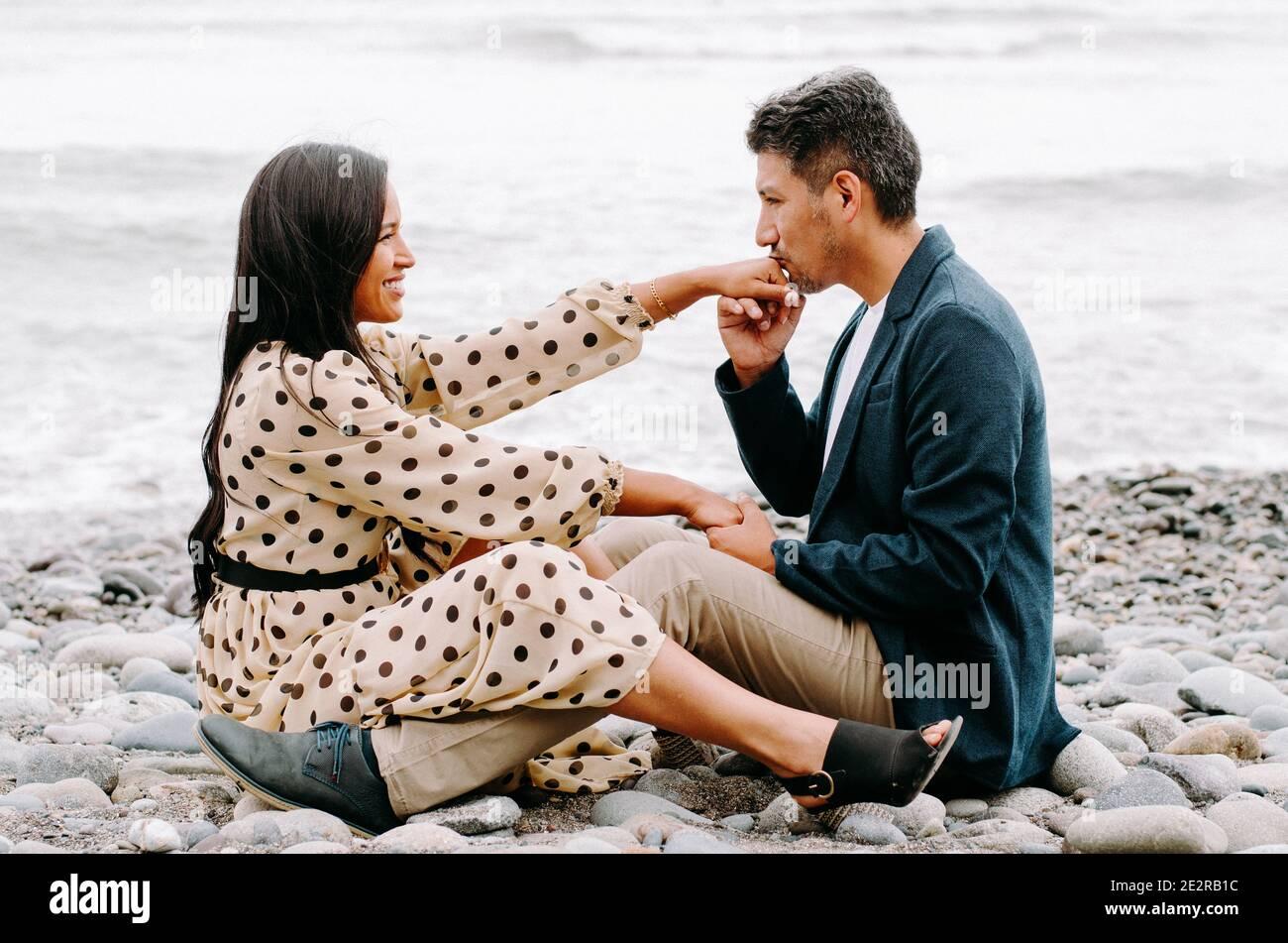 Junges Paar in der Liebe, attraktive Mann und Frau genießen ein romantisches Date am Strand, Mann küssen Frau die Hand Stockfoto