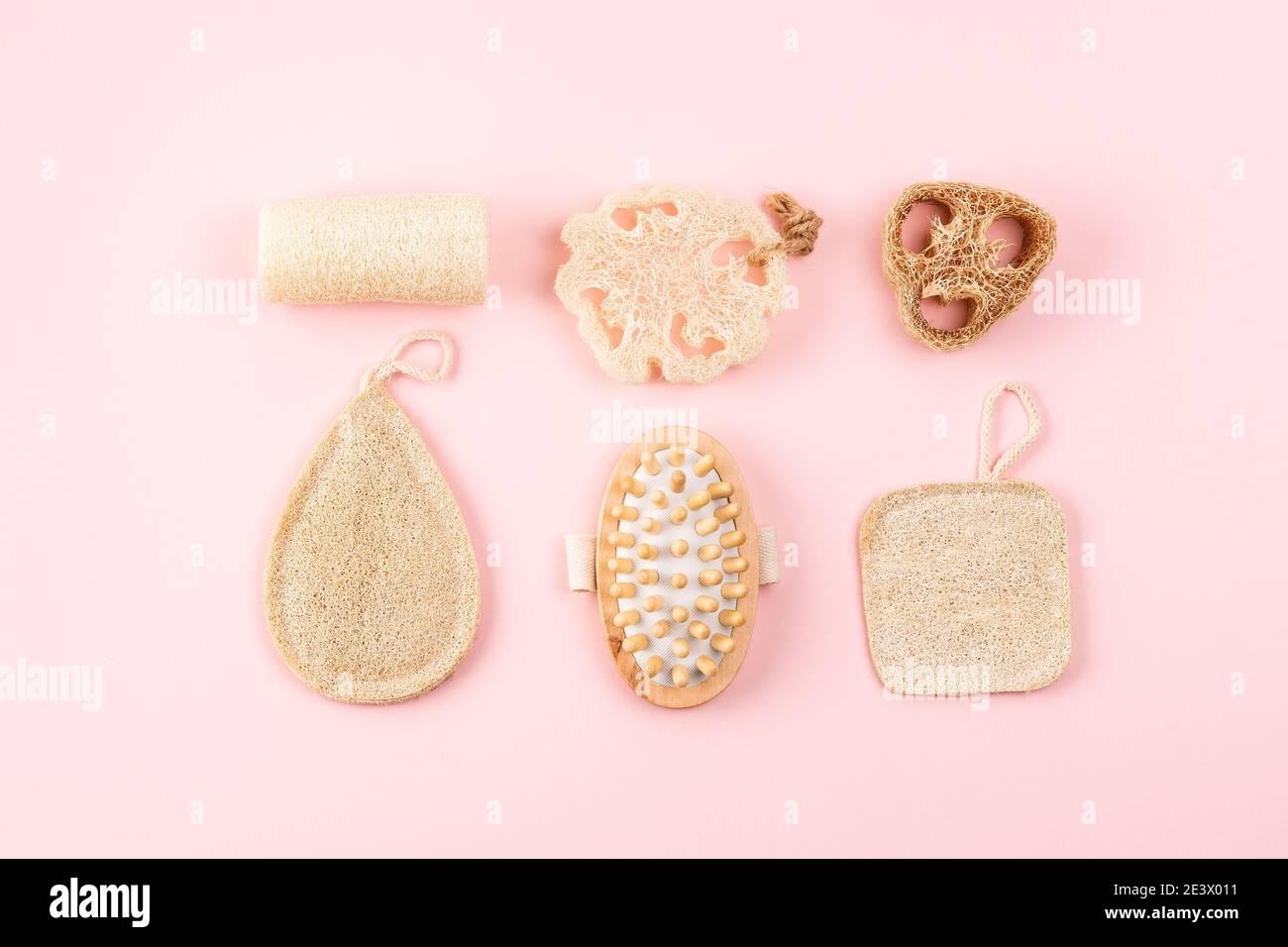 Bad-Accessoires, Naturlöffelschwamm, Holzbürste auf rosa Hintergrund. Zero Waste und plastikfreies Konzept, nachhaltiges Bad und Lifestyle Stockfoto