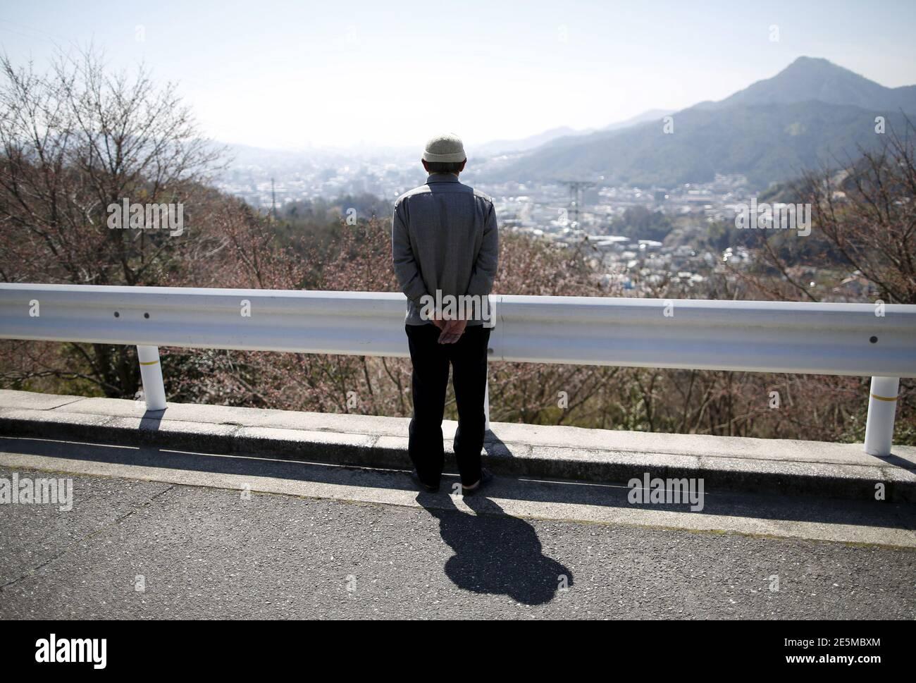 Fumiaki Kajiya, ein 76-jähriger Atombombenüberlebender und pensionierter Schullehrer, blickt von der Straße vor seinem Haus in Hiroshima, Westjapan, 27. März 2015 in Richtung Stadtzentrum. Als der 70. Jahrestag des ersten Atomangriffs der Welt ansteht, empfinden es viele Überlebende noch immer als zu schmerzhaft, darüber zu sprechen. Doch mit schwindenden Reihen sind andere entschlossen, ihre Erfahrungen an jüngere Generationen weiterzugeben. Ein US-Bomber warf die Atombombe am 6. August 1945 auf Hiroshima ab und tötete Ende des Jahres etwa 140,000 von den 350,000, die in der Stadt lebten. Die Stadt hat immer noch som Stockfoto