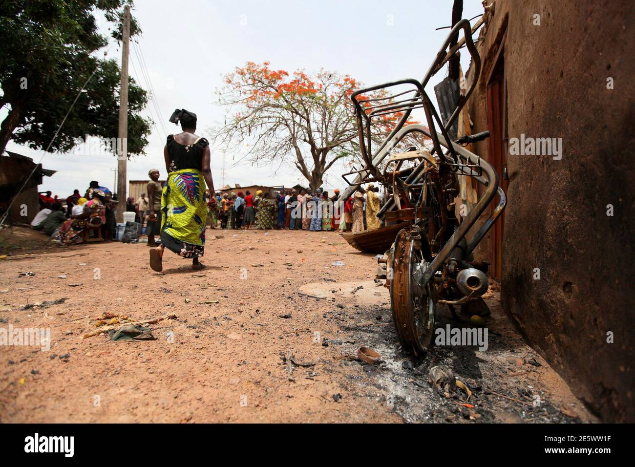 Eine Frau geht vorbei an einer verbrannten Motorrad Wahlrecht an einem polling Unit in Kachia Dorf, wo Gewalt in Nigeria die nördlichen Bundesstaat Kaduna 28. April 2011 letzte Woche brach. Wähler sickerte heraus zu Wahllokalen am Donnerstag in zwei Bundesstaaten im Norden Nigerias, wo Hunderte Ausschreitungen letzte Woche unter den wachsamen Augen der Polizisten und Soldaten Besatzung Barrikaden getötet. REUTERS/Afolabi Sotunde (NIGERIA - Tags: Politik-Wahlen-Unruhen) Stockfoto