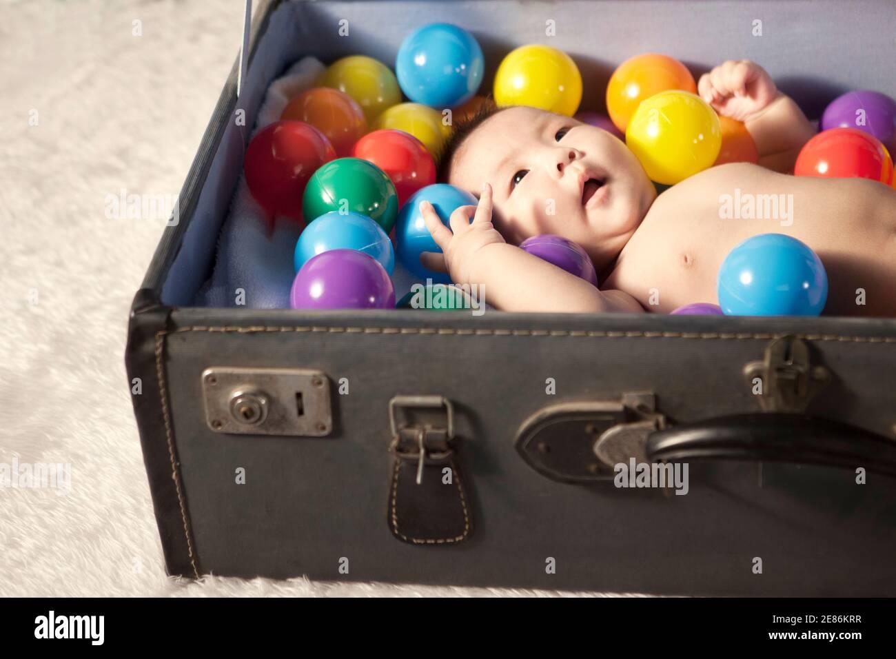 Ein Baby, das sich mit Farbkugeln im Koffer legt Hochwertige Fotos Stockfoto