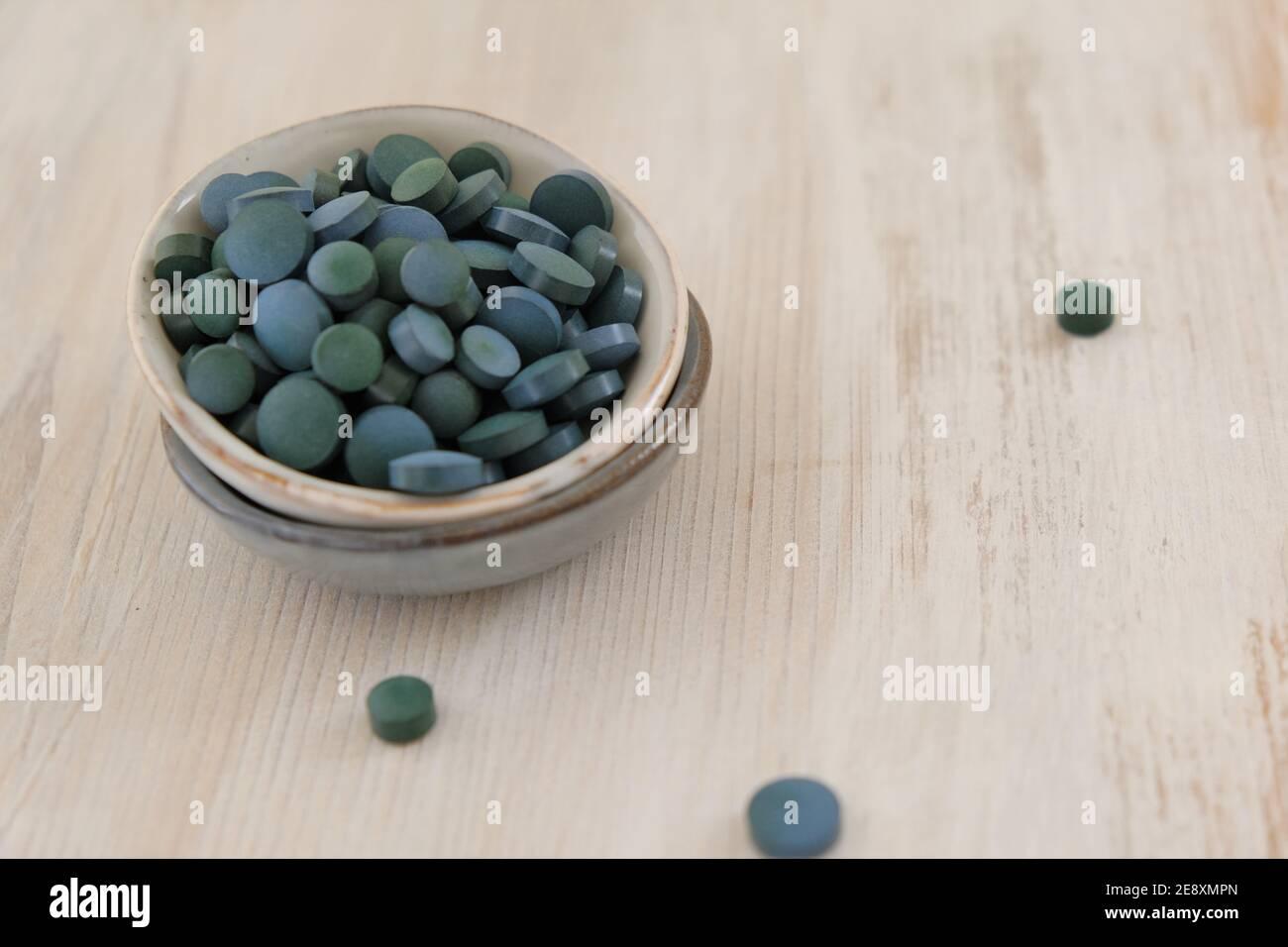 Spirulina Algen grün in Tabletten in runden Keramikbecher auf einem hellen Holz schäbigen Hintergrund..Nahrungsergänzungsmittel.Super Nahrung. Gesunde Bio-Algen Stockfoto
