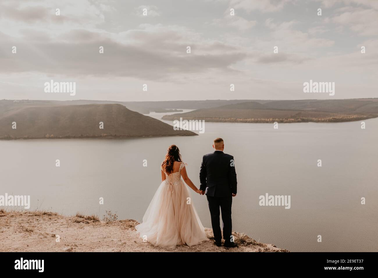 Liebevolles Paar Hochzeit Brautpaar in weißem Kleid und Anzug Spaziergang im Sommer auf dem Berg über dem Fluss. Sonnenuntergang und Sonnenaufgang. Mann und Frau auf Felsen über der Klippe Stockfoto