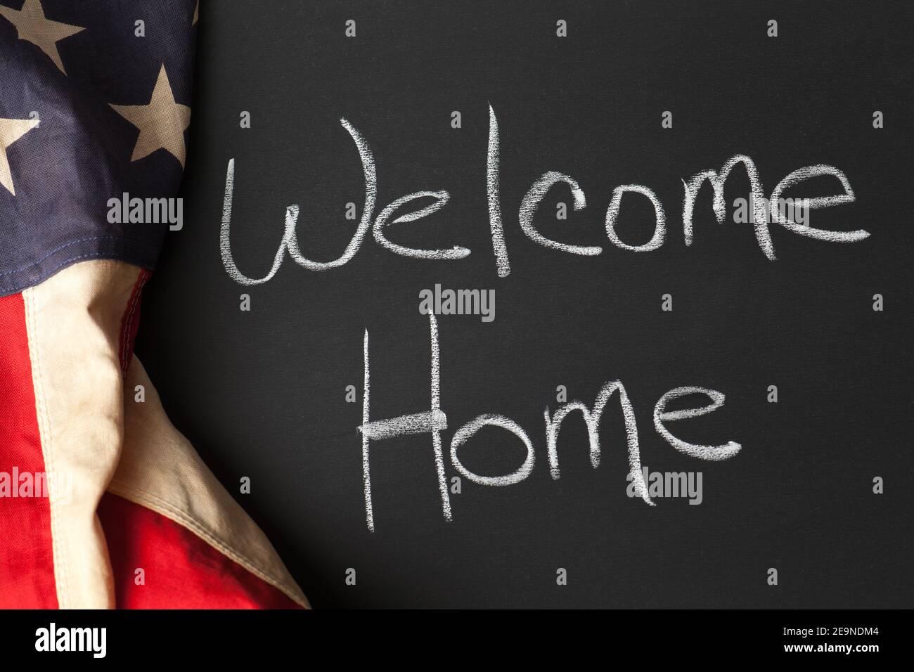 Willkommen zu Hause geschrieben auf einer Tafel mit Vintage amerikanischen Flagge Stockfoto