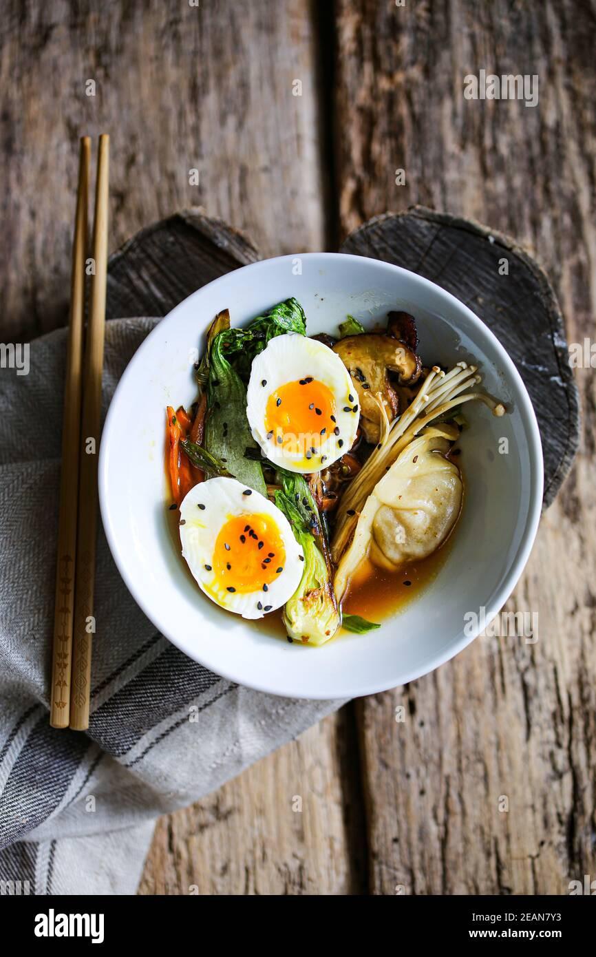 Shiitake-Brühe mit gebratenem Gemüse und Jiaozi-Knödeln Stockfoto
