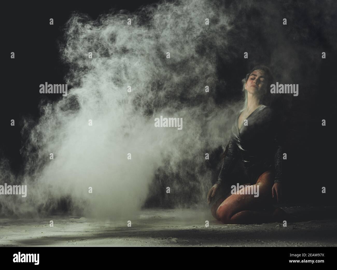 Junge schöne kaukasische Frau mit langen Haaren ist in gekleidet Ein sportlicher schwarzer Body und sitzt auf dem Boden Stockfoto